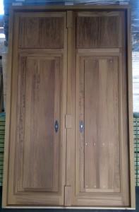 Puerta de entrada en madera de Iroko sin barnizar, formada por un fijo superior y dos hojas abatibles y con cerraduras independientes.