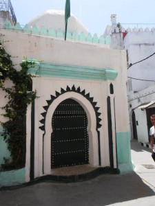 Puerta de entrada en forma de arco y con clavos.A