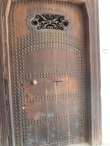 Puerta de entrada con clavos y reja.