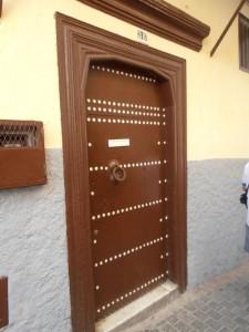 Puerta de madera con clavos y tirador.